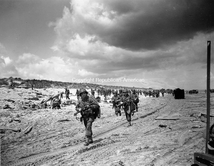 American infantrymen follow in the tracks of tanks as they march along the beach, during Allied Normandy landing operations in France, June 9, 1944.  (AP Photo/Peter Carroll)