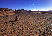 Libya, Tuareg man prays in the plain desert at sunset