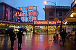 Seattle, Pike Place Farmer's Market, Historical District, Washington State, Pacific Northwest, USA, Central and Sanitary Arcades, Saturday morning set up at the vegetable stands and fish markets, neon signage, reflected across First Avenue, the Market was founded in 1907.