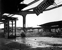 Alert for enemy movement, Pfc. Armand Rindone, Philadelphia, Pa., crouches with a carbine at the railroad station in the newly captured town of Hamm, Germany.  April 6, 1945.  T4c. Vernon M. Sharette. (Army)<br /> NARA FILE #:  111-SC-203836<br /> WAR & CONFLICT BOOK #:  1093
