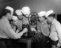 Instructor in class 4 at Naval School of Photography training students in operation of motion picture projector.  J.D. Epply, PhoM 1/c, on the Ampro 16mm Sound Motion Picture Camera.