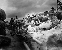 Marines take cover behind a sea wall on Red Beach #3, Tarawa.   November 1943.  (Marine Corps)<br /> Exact Date Shot Unknown<br /> NARA FILE #:  127-GR-119-64002<br /> WAR & CONFLICT BOOK #:  1180