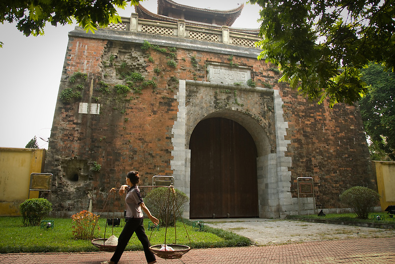 A young girl carries her rice baskets over her shoulder walking past a chinese building. The Chinese occupied Vietnam for over a thousand years. Vietnam is often looked at as a house with it's windows open. They've had many different countries occupy them over the years -- blowing their winds through the house. They'll come, move things around and add a bit, but Vietnam has managed to keep its own culture while also incorporating some of those from their visitors.