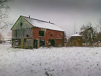 Pal Pre photo of snow covered barn and rolls of hay on a farm.