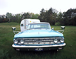 A light blue 1963 Mercury Monterey pulling a white 1963 Fleetwing canned ham vintage travel trailer.