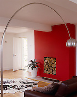 The fully working fireplace is also used to store logs during the summer, the chimney breast painted a strong red to contrast with the rest of the room *** Local Caption *** Arco lamp