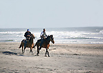 Two men ride horses on the beach