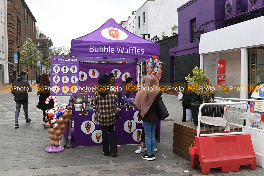 People queue at a waffle stall in Camden Town as the COVID-19 lockdown restrictions start to ease across the UK on 2nd April 2021