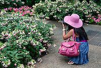 Woman composing a picture at a public garden.