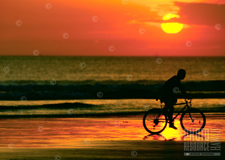 Solitary Cyclist Pedals Down The Beach At Sunset