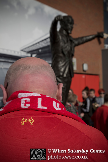 A fan bows his head in front of the Bill Shankly statue after the 25th anniversary memorial service to the 1989 Hillsborough disaster at Liverpool Football Club's Anfield Stadium. The Hillsborough stadium disaster led to 96 Liverpool football fans losing their lives in a crush at an FA Cup semi final tie against Nottingham Forest. The families of the victims campaigned against the original verdict of the incident and were rewarded with a new inquiry held in 2014 into events at the match at Hillsborough. Photo by Colin McPherson.