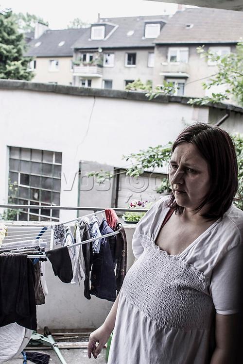 Mutter macht Zigarettenpause auf dem Balkon ihrer Wohnung, Waeschestaender, Hartz IV, Bochum<br /> <br /> <br /> *** HighRes auf Anfrage *** Voe nur nach Ruecksprache mit dem Fotografen *** Sonderhonorar ***<br /> <br /> Engl.: Europe, Germany, Bochum, unemployment benefit, Hartz IV, unemployed, unemployment, poverty, poor, social benefits, mother, balcony, smoking, portrait, 20 June 2012<br /> <br /> ***Highres on request***publication only after consultation with the photographer***special fee***