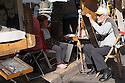 Paris, France. 09.05.2015. Old, male artist paints young girl, Place du Tertre, Montmartre, Paris, France. Photograph © Jane Hobson.