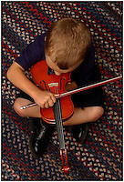 A boy plays a small violin while sitting on a colorful rug. Photo taken from overhead. Can be used to illustrate children and music. Model release.