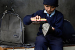 A young boy shines his shoes as he gets ready for school at an orphange in Pokhara, Nepal.