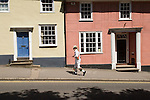 Morris Dancer walking up Bolford Street past traditional Essex homes. Thaxted, Essex England. 2006