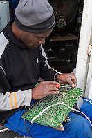 South Africa, Cape Town, Guguletu Township.  Man Soldering a Circuit Board.
