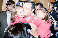 "Campaign staffers look on while Texas senator and Republican presidential candidate Ted Cruz holds his two daughters Catherine (left) and Caroline after speaking at an event called ""Smoke a cigar with Ted Cruz"" at a house party at the home of Linda & Steven Goddu Salem, New Hampshire. Cruz briefly smoked a cigar after speaking at the event."