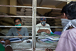 Government workers at emergency duty at a government controlled ration shop in New Garia during 21 days lock down in India due to covid 19 pandemic. Kolkata, West Bengal, India. Arindam Mukherjee.