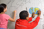 Public elementary school for the gifted grades K-6: girl and a boy working on large scale map on wall using map in book