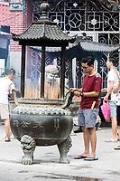 George Town, Penang, Malaysia.  Young Man Preparing Joss Sticks (Incense) outside Goddess of Mercy Temple, Kuan Yin Teng, Kong Hock Keong.