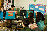 Education Elementary school Grade 2 group of boys and girls using classroom computers horizontal