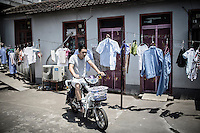 A man rides his scooter past a line of laundry in Xingxing village on the outskirts of Shanghai,  China on 14 August 2015.  As China's sputtering economy has beginning to affect employment, many migrants who used to live in the village to work on Shanghai's numerous construction sites and factories are beginning to thin out.