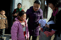 Representatives from the Chinese charity the Amity Foundation gives donated clothing to the orphans Zhao Min, 9, and brother Zhao Shi, 6, outside their home in Qingdun Village, Gangyun County, Jiangsu, China, as grandmother Sun Zhan Xia looks on.  The orphans have lived with their grandparents Sun Zhan Xia (female) and Zhao Xia You (male) since 2007 when the children were orphaned in 2007. The children's father, Sun Zhan Xia's son, died of hepatitis in 2006 and their mother was forced to remarry and abandon the children in 2007.  Sun Zhan Xia and her husband are both over 60 and in bad health.  The couple owes approximately 40,000 RMB (about $5,300 USD) to pay for the medical treatment of their dead son, the children's father.  Due to their health situation and this enormous debt, the pair cannot afford to care for the children any longer, and the children are in danger of being placed in orphanages.  ..At the time of the picture, China's Amity Foundation charity, was investigating the family's situation in preparation to raise money to financially support these children and other orphans in similar situations.  With Amity's support, each orphan, aged 6-12, would receive approximately 1,400 RMB annually (about 200 USD) to pay for the cost of living. Amity works to keep children out of the institutional orphanages in China, preferring to provide monetary assistance that can help maintain a family environment for the orphans it helps.