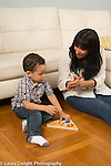 2 year old toddler boy with mother at home putting puzzle together mother clapping at his accomplishment