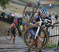 Puck Pieterse of the Netherlands carries her bicycle Wednesday, Oct. 13, 2021, while competing in the Union Cycliste Internationale Cyclo-cross World Cup at Centennial Park in Fayetteville. The city was one of 16 sites around the globe to hold a world cup event this year for Union Cycliste Internationale, known as International Cycling Union in the United States. Fayetteville will host the UCI World Championships at Centennial Park Jan. 28-30. Visit nwaonline.com/211014Daily/ for today's photo gallery.<br /> (NWA Democrat-Gazette/Andy Shupe)