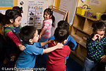 Educaton preschool  3-4 year olds movement dancing exercise group of children dancing to music moving with hands on each other's shoulders sad girl in foreground not participating crying rubbing her eye  horizontal