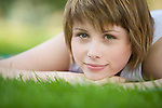 A beautiful girl lies on the green grass in a park.