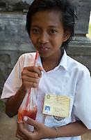 Bali, Indonesia.   Teenage Schoolgirl with a Juice Drink.  Tenganan Village.