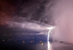 Pictured:  A storm in Trieste, Italy<br /> <br /> Lightning from a huge supercell storm strikes the ocean and illuminates the sky as boats float on the calm water.  In another image enormous clouds gather over a city as they crackle with forks of electric light.<br /> <br /> The supercells can last for up to ten hours and can cause devastating tornadoes and torrential hailstone-filled thunderstorms.  The stunning images were taken in Padova and Trieste in Italy and in Ljubljana, Dloneja vas and Crni Kal in Slovenia by weather information supervisor and amateur photographer Marko Korosec.  SEE OUR COPY FOR DETAILS.<br /> <br /> Please byline: Marko Korosec/Solent News<br /> <br /> © Marko Korosec/Solent News & Photo Agency<br /> UK +44 (0) 2380 458800
