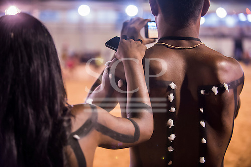 A young Xerente warrior films the games on his smart phone with is girlfriend next to him during the International Indigenous Games, in the city of Palmas, Tocantins State, Brazil. Photo © Sue Cunningham, pictures@scphotographic.com 27th October 2015