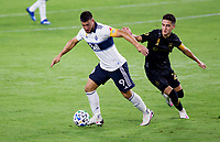 LOS ANGELES, CA - SEPTEMBER 23: Lucas Cavallini #9 of the Vancouver Whitecaps moves past Eduard Atuesta #20 of LAFC during a game between Vancouver Whitecaps and Los Angeles FC at Banc of California Stadium on September 23, 2020 in Los Angeles, California.
