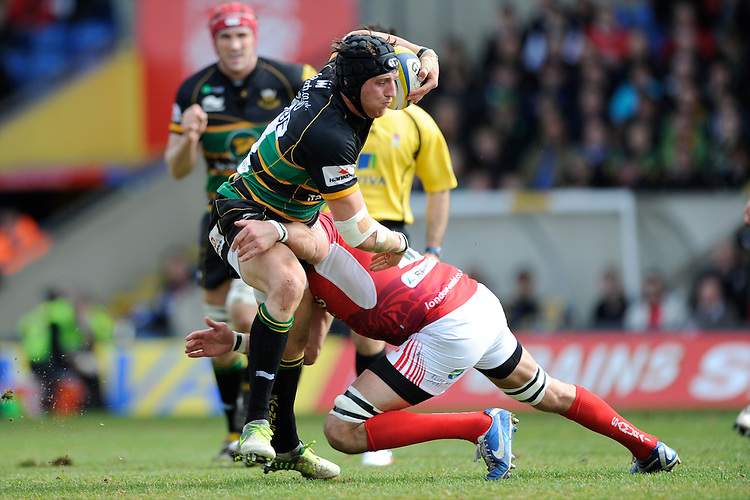 Tom Wood of Northampton Saints is tackled by Julio Cabello Farias of London Welsh during the Aviva Premiership match between London Welsh and Northampton Saints at the Kassam Stadium on Sunday 14th April 2013 (Photo by Rob Munro)