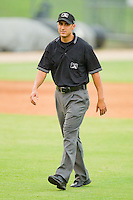 Umpire Derek Mollica handles the calls on the bases during a South Atlantic League game between the Asheville Tourists and the Kannapolis Intimidators at Fieldcrest Cannon Stadium July 26, 2010, in Kannapolis, North Carolina.  Photo by Brian Westerholt / Four Seam Images