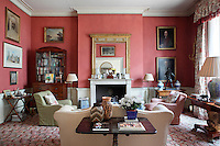 A traditional sitting room with a high ceiling and furnished with antique furniture. The room has a gilt mirror above the fireplace, a sofa, armchairs and a variety of paintings are displayed on the walls.