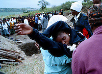 A mourner collapses at the graveside during the funeral of three brothers. The three, aged 18, 19 and 25, were killed by gunmen who burst into their house. One of the brothers was a member of the African National Congress (ANC). The Mandini area falls under the control of a chief aligned with the Inkatha Freedom Party (IFP). Political violence in the province had increased in the run-up to the country's first multiracial election.
