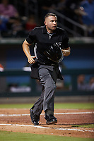 Home plate umpire Jonathan Parra hustles down the first base line during the game between the Norfolk Tides and the Charlotte Knights at Truist Field on August 19, 2021 in Charlotte, North Carolina. (Brian Westerholt/Four Seam Images)