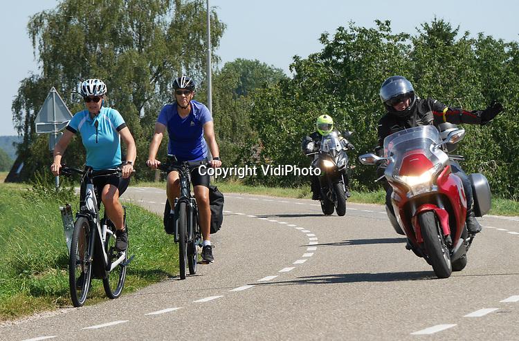 Foto: VidiPhoto<br /> <br /> RANDWIJK – Ondanks dat de protestrit van boze motorrijders door onder andere de regio Utrecht werd afgeblazen door de organisatie vanwege de hitte, gingen veel motorrijders zaterdag op eigen initiatief toch de weg op. Zo liet de landelijke motorclub CMV Op Weg hun geplande toertocht door onder andere Utrecht gewoon doorgaan en ook andere motorrijders toerden op eigen initiatief over de Nederlandse dijken, zoals hier in de Betuwe, al dan niet uit protest tegen het afsluiten van dijkwegen voor motoren in diverse gemeenten. De officiële protestdag is nu verplaatst naar 20 september.