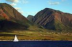 A sailboat cruises along the Maui coast.