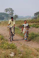 A man cycles past a women on a small dirt track on the outskirts of Kolkata<br /> <br /> To license this image, please contact the National Geographic Creative Collection:<br /> <br /> Image ID: 1925836 <br />  <br /> Email: natgeocreative@ngs.org<br /> <br /> Telephone: 202 857 7537 / Toll Free 800 434 2244<br /> <br /> National Geographic Creative<br /> 1145 17th St NW, Washington DC 20036