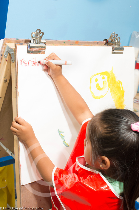 Education Preschool 4-5 year olds girl in smock writing her name painting with marker