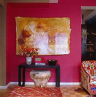 A large artwork hangs on the bright pink wall of the living room above a wooden console table