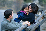 A family of three having fun at a wooden rail fence near Lumpy Ridge, Rocky Mtns, CO