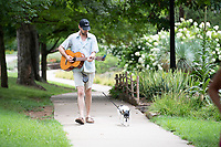 Adam Hughes, of Fayetteville, walks with his dog Annie Sunday Aug. 1, 2021 at Wilson Park in Fayetteville. Hughes likes to practice playing guitar but has trouble finding time for it so he plays while walking the dog. Visit nwaonline.com/21000802Daily/ and nwadg.com/photo. (NWA Democrat-Gazette/J.T. Wampler)