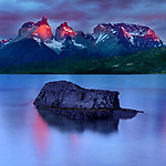 Reflection in Lago Pehoe and dramatic light at sunrise on the Towers and Central Massif of Torres del Paine. Torres del Paine National Park, Patagonia, Chile.