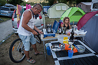 Switzerland. Canton Ticino. Tenero. Camping Campofelice. The father Bernard Nussbaumerr (L) and his daughter Lumia (R) are Swiss citizens from the canton of Jura. They both sleep in two different tents. Campers are restricted to designated sites for which fees are payable. The man turns on with lighter the gas stove to cook coffee in a Moka pot while the teenage girl seats on a chair. The moka pot is a stove-top maker that brews coffee by passing boiling water pressurized by steam through ground coffee.  21.07.2018 © 2018 Didier Ruef